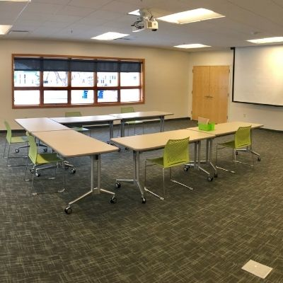 RCU Community Room. Large meeting room with window showing tables and chairs with a projector and retractable screen.